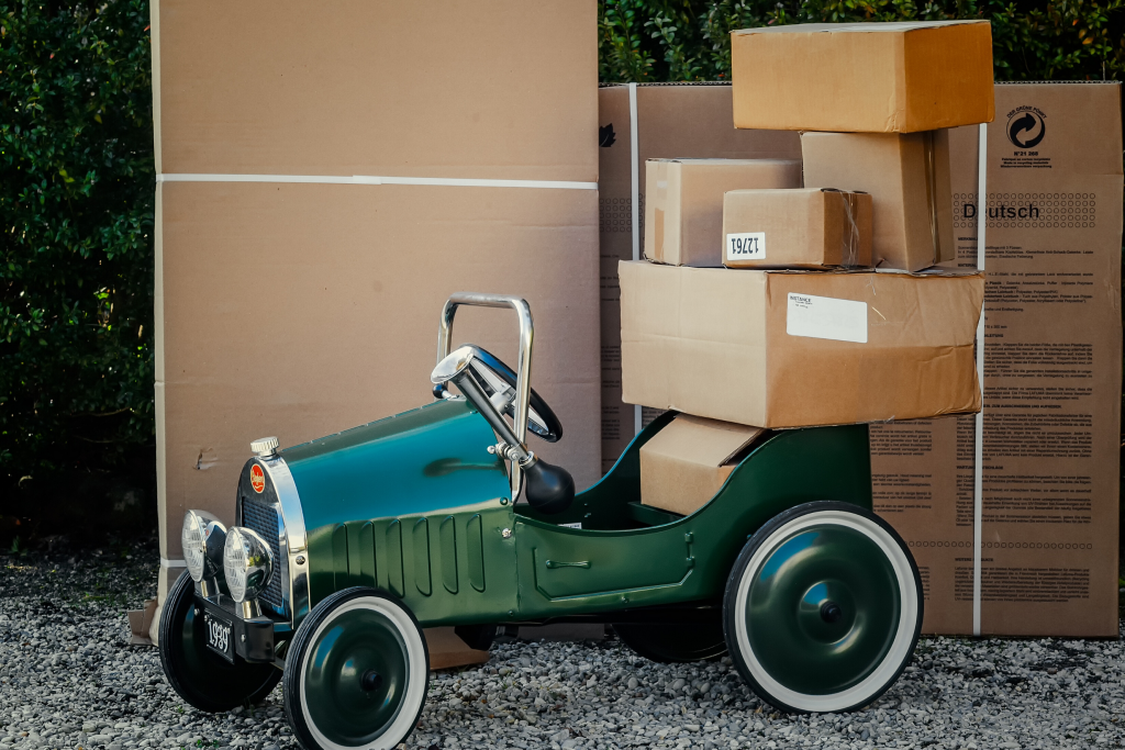 A green vintage car loaded with boxes