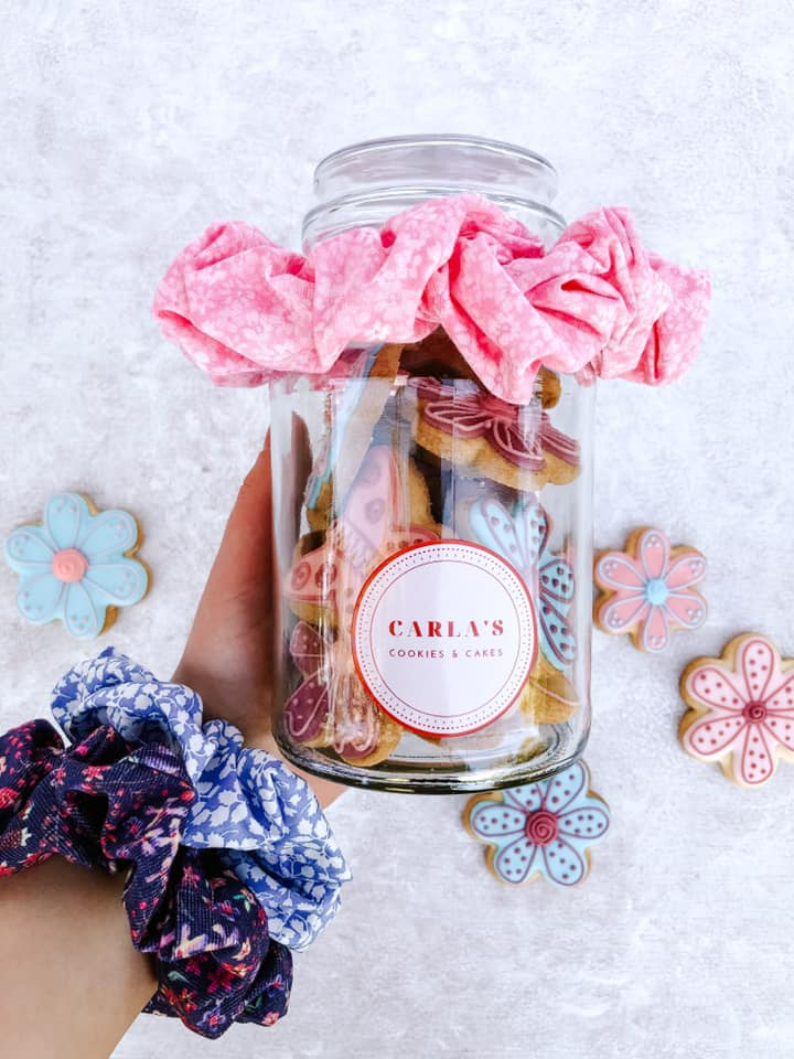 Hand holding glass jar filled with cookies by Carla's Cookies and Cakes