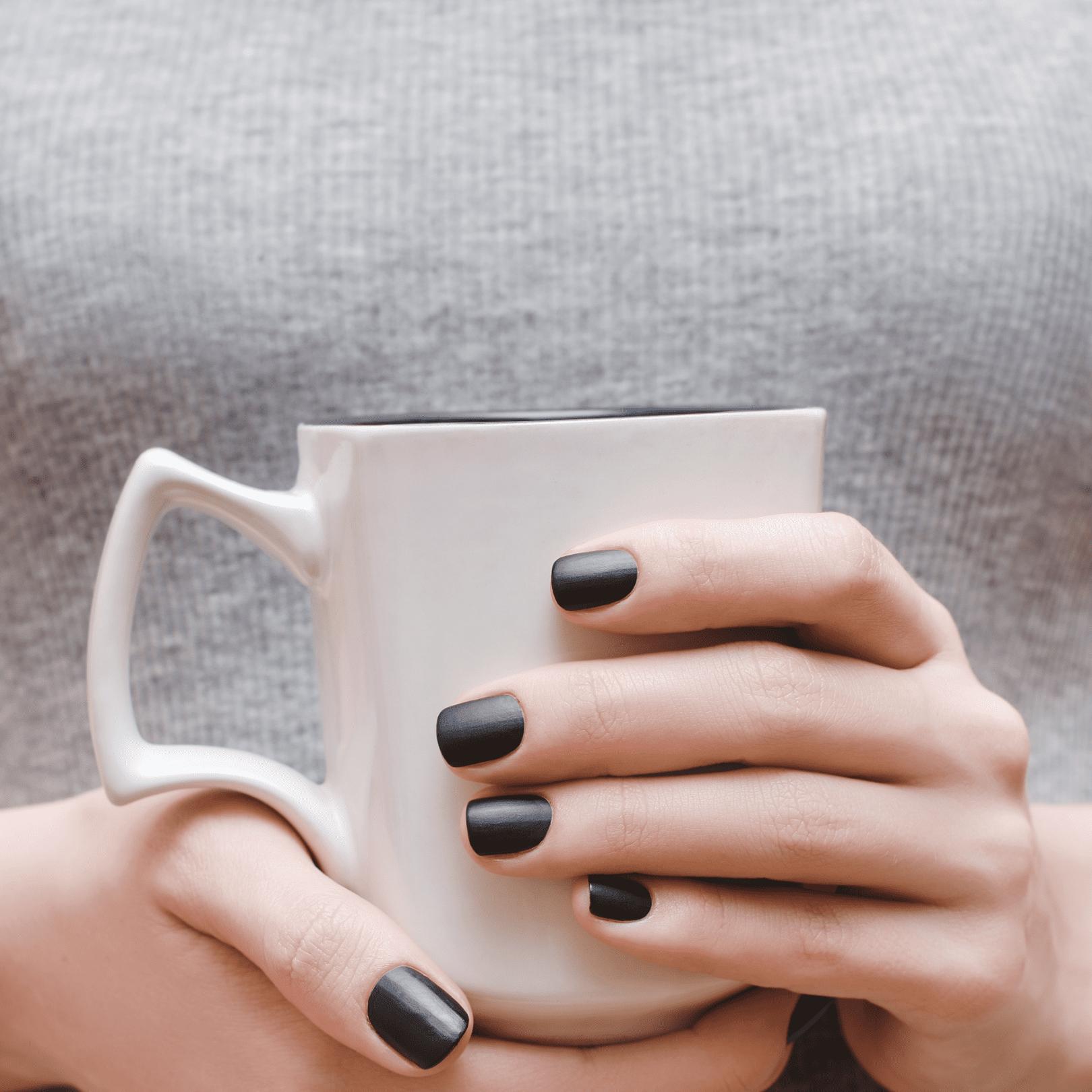 Woman with matte black manicured nails holding coffee mug