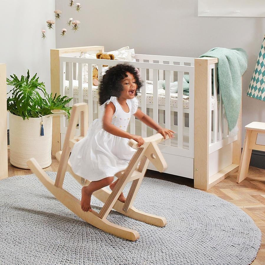 Young girl on rocking horse in nursery by CLM Home