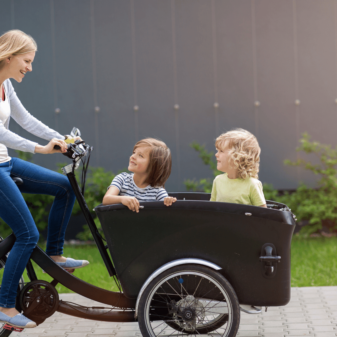 Woman driving bicycle with cart carrying two children in front
