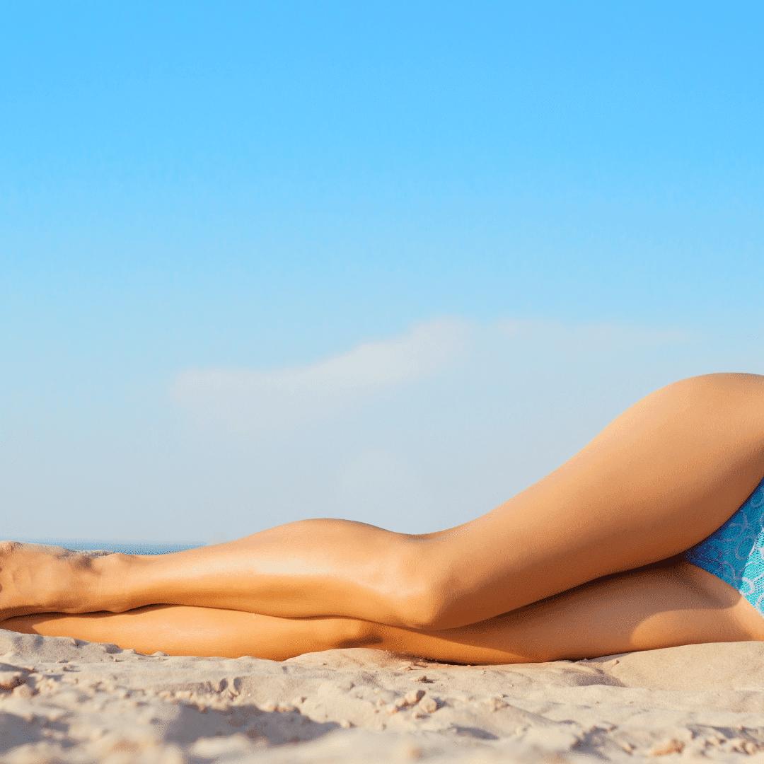Woman with waxed legs lying on beach