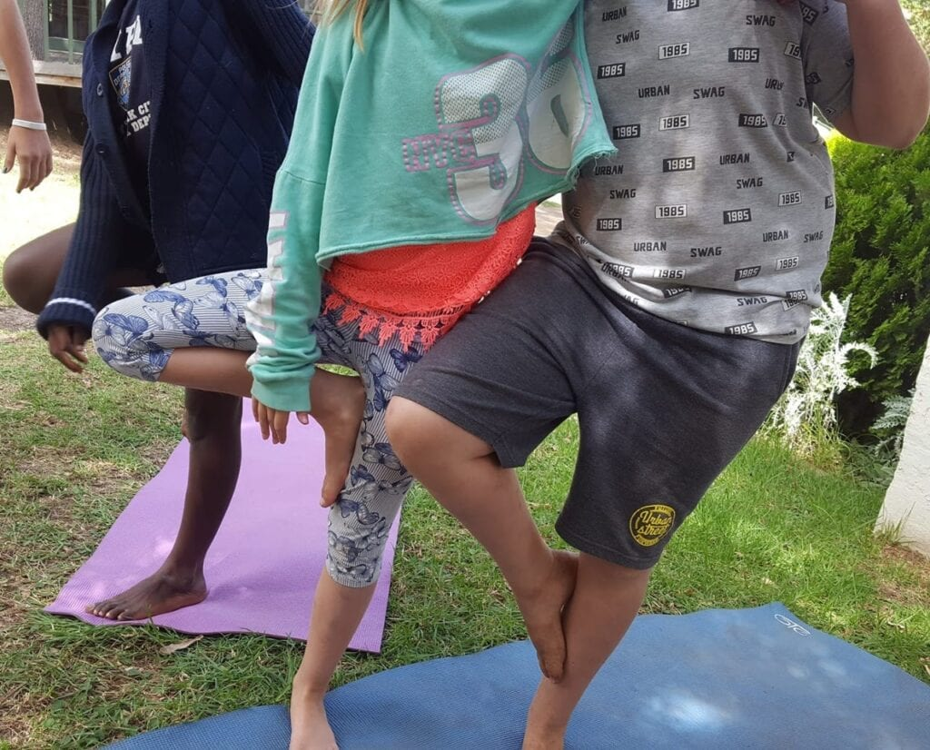 A group of young children taking yoga lesson