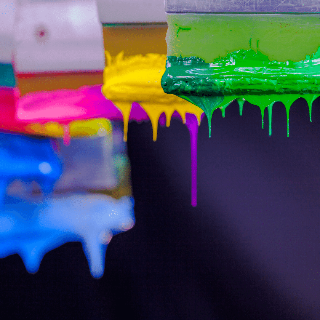 Closeup of paintbrushes dripping with coloured paint