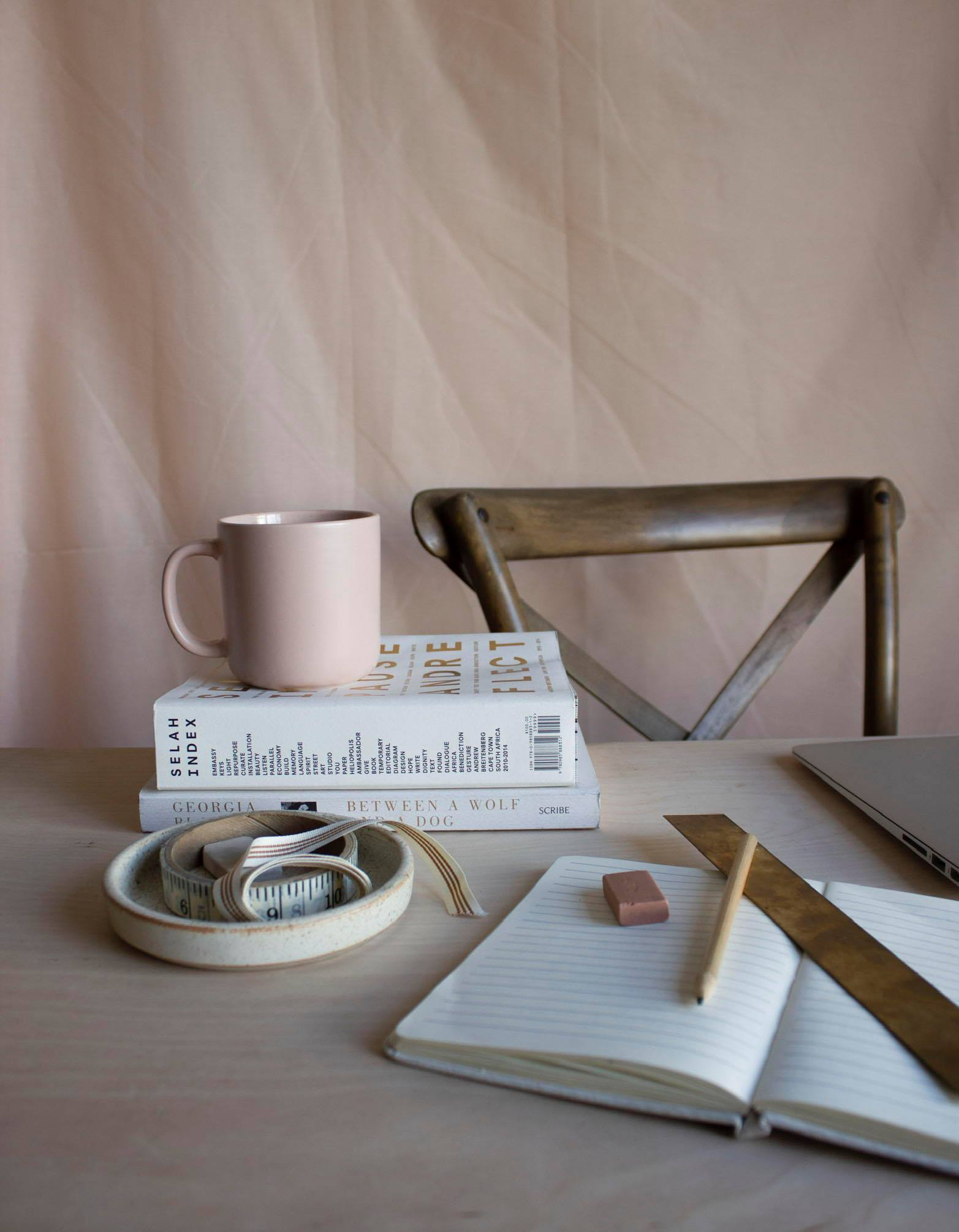 Setup of an open book, a big closed book with a pink cup on it by Natascha Mostert Studio