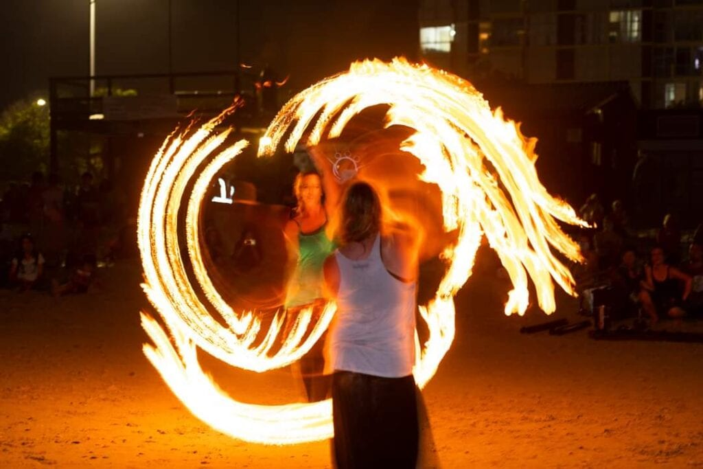 Two female fire dancers from Fire and Flow Studio performing a fire dance at night on the beach