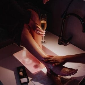 A woman getting a foot massage while holding a glass of sparkling wine at Nuūdo Luxury Express Spa