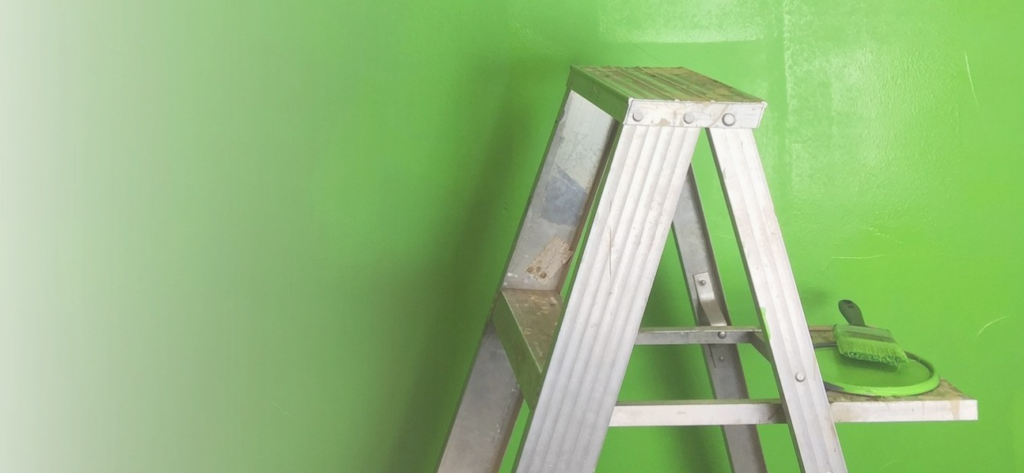 Silver ladder against bright green wall