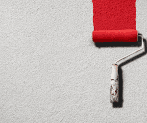 Paint roller with red paint against white wall