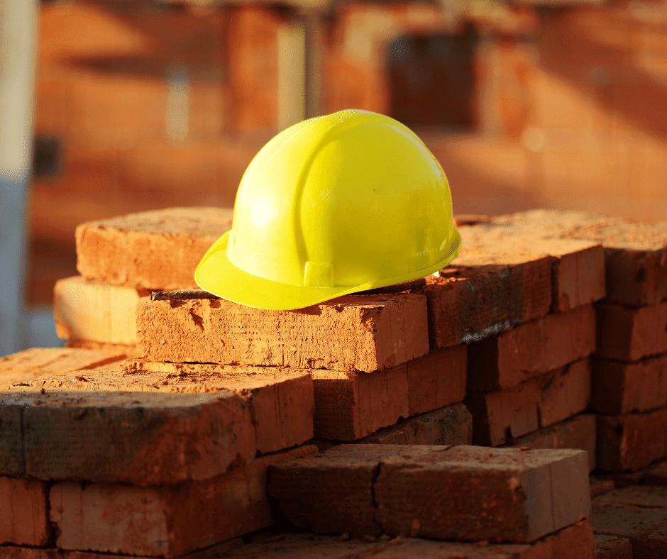 Yellow hard hat on top of a pile of bricks