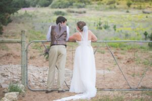 Groom and bride leaning over a gate on a farm
