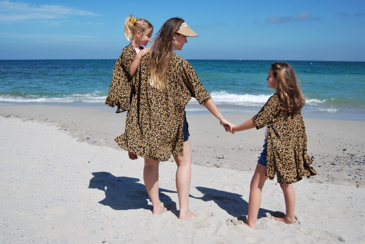 A woman and two girls wearing Hello Yello kimonos on beach in Strand