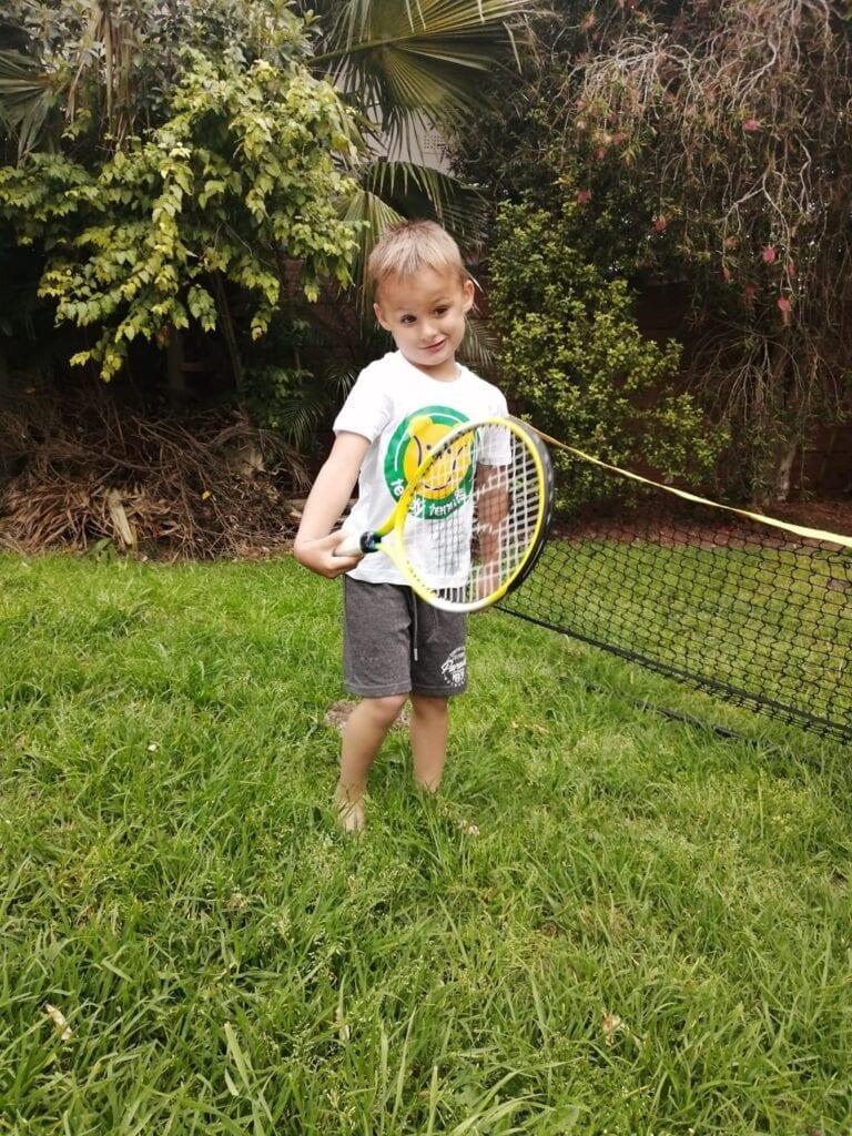 Young blonde boy wearing white Teddy Tennis t-shirt