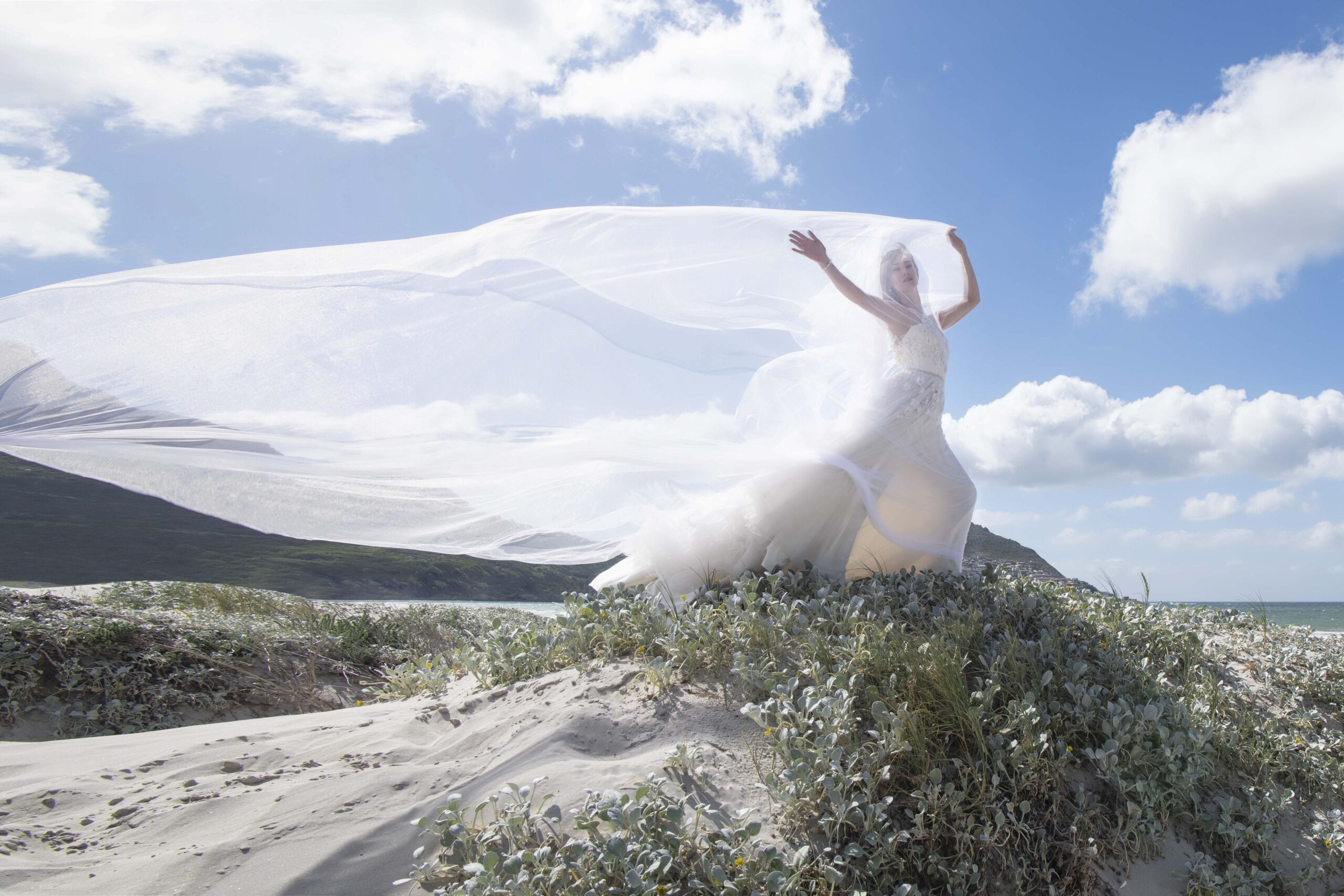 Woman in dress standing on dune