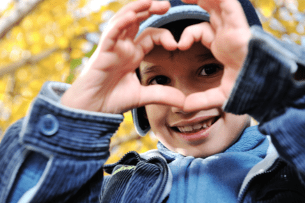 Boy making a heart with his fingers