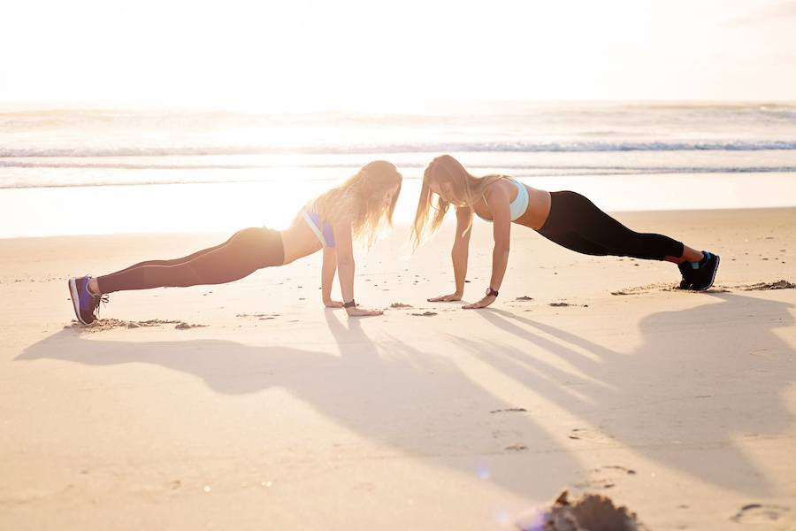 Two women exercising on the beach