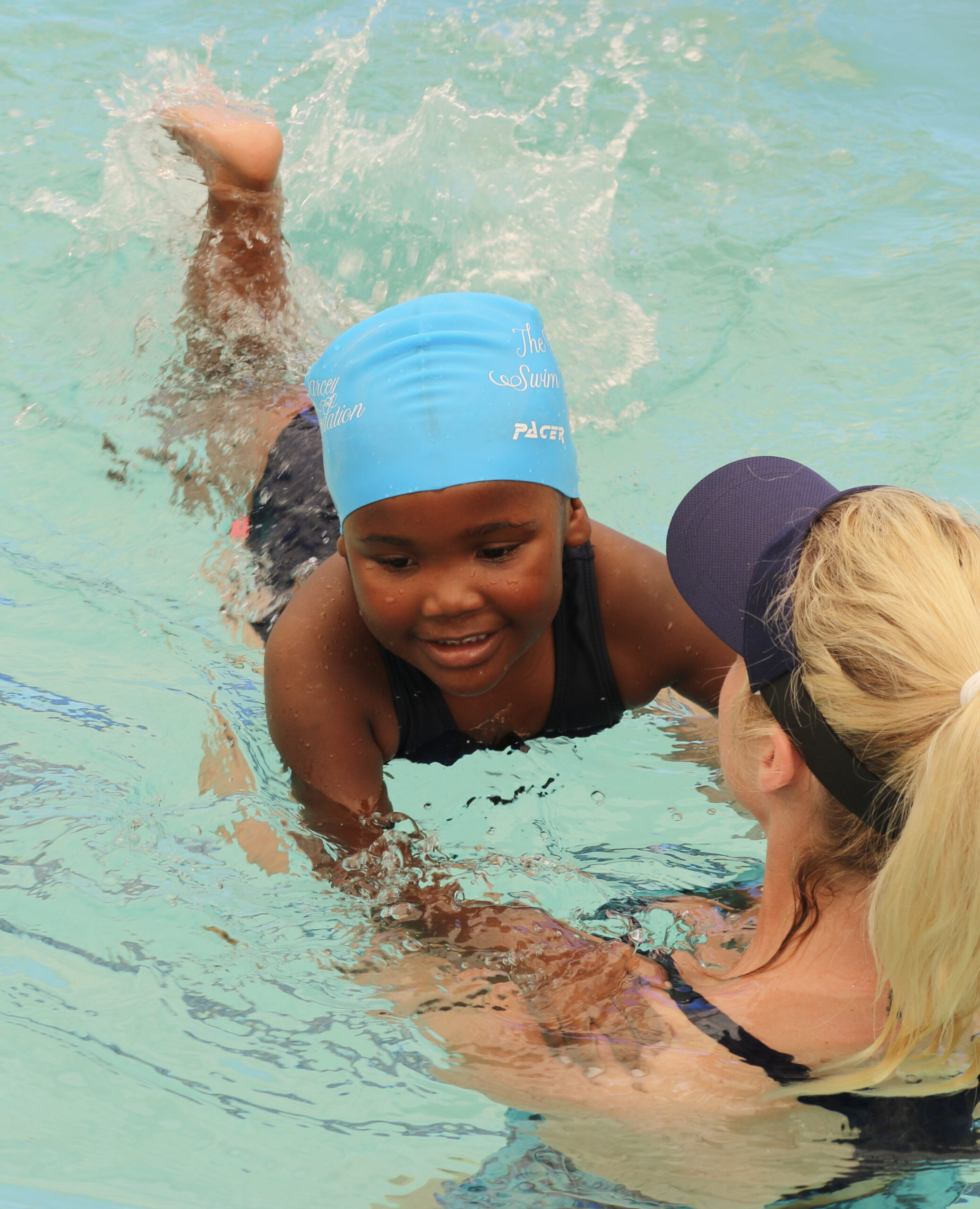 A volunteer from The Darcey Sunshine Foundation giving a young child a swimming lesson