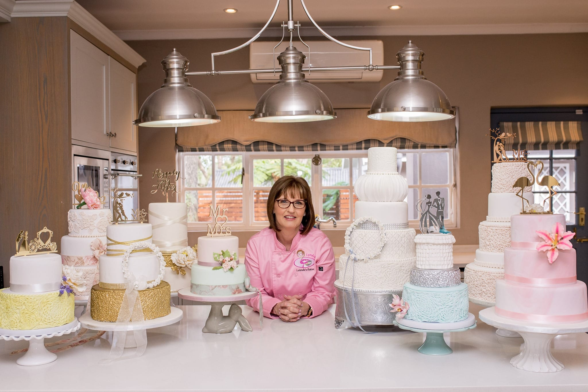 Lyndsay from Lullubelle's Bakes sitting in kitchen surrounded by celebration cakes