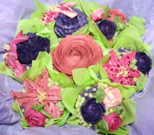 A cupcake bouquet with flowers made by Bakes and Cakes