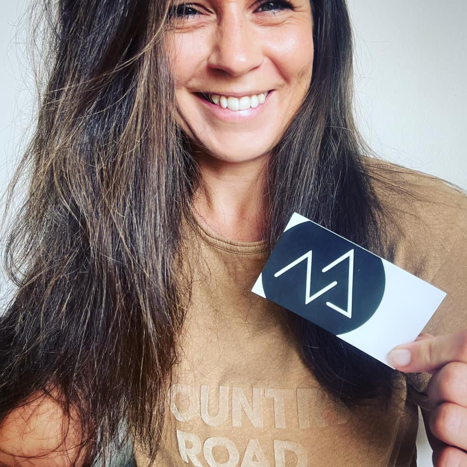 Owner of Summit4Marketing Greta smiling and holding her business card