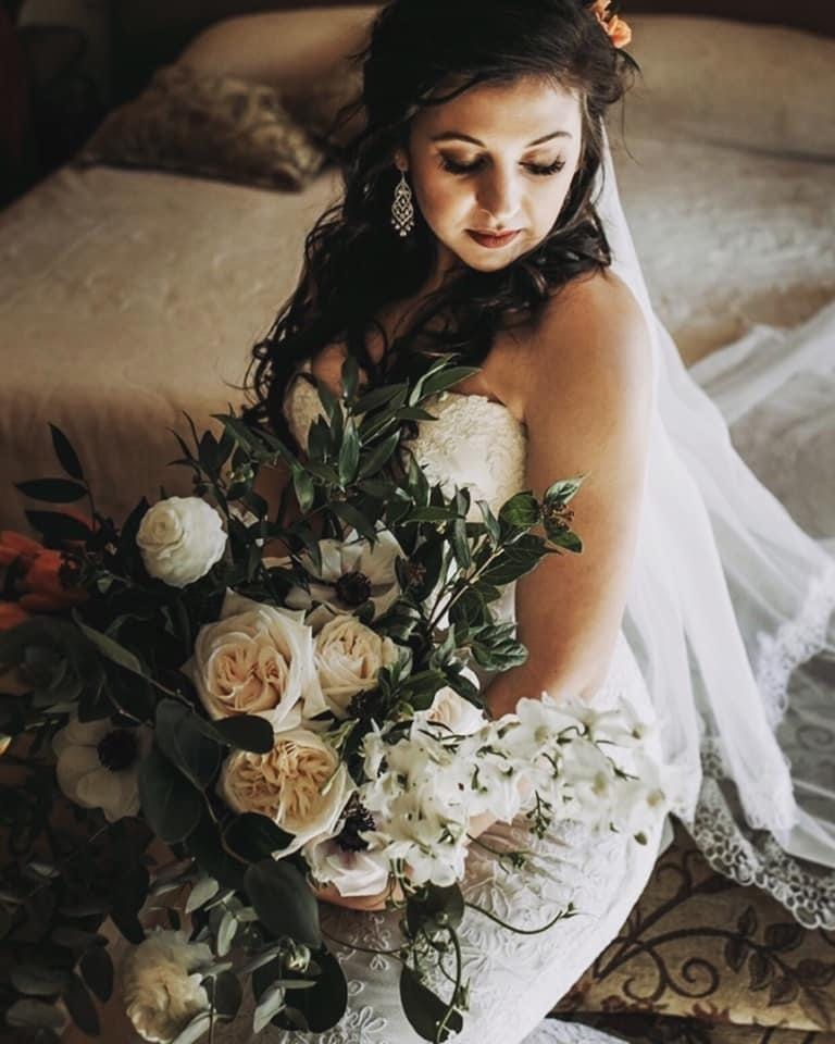 A bride holding a bouquet by Simply Floral
