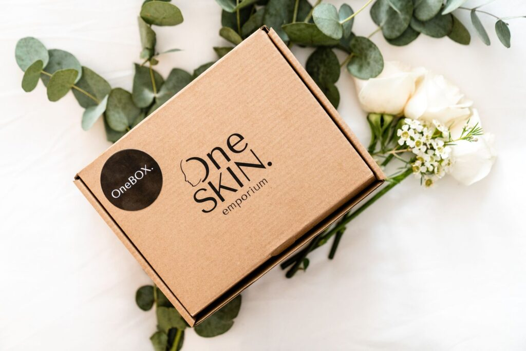 A brown OneSKIN emporium subscription box with leaves and flowers around it