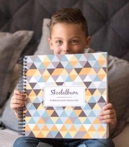 A boy holding a school album by The Album Company