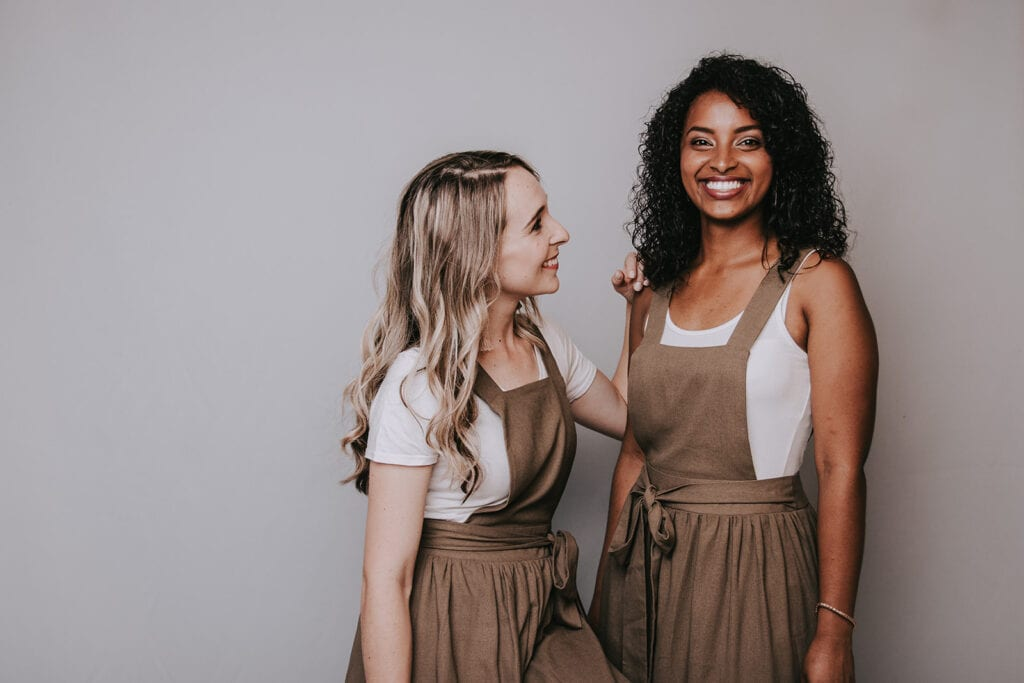 Two young women dressed in brown dresses by Juffie Clothing