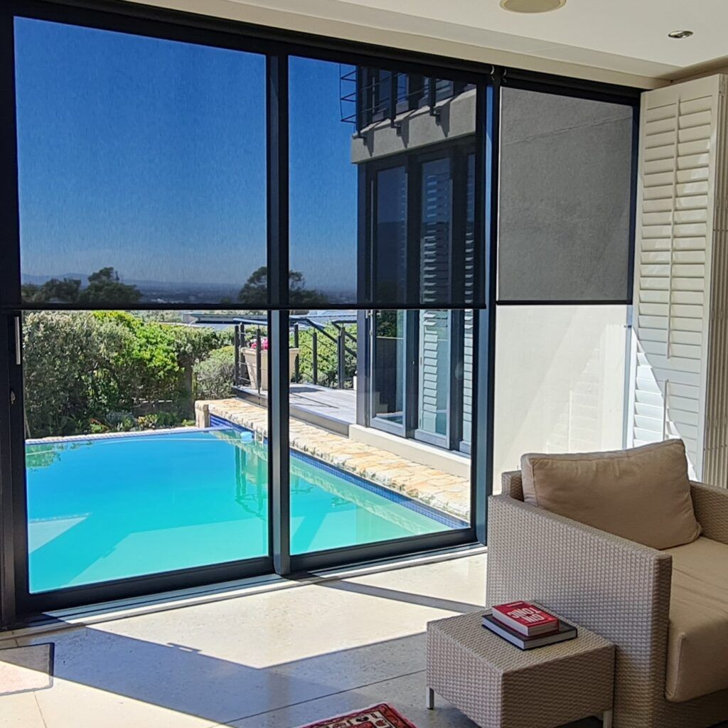 Blinds installed by APL Finishes in front of large window overlooking a pool