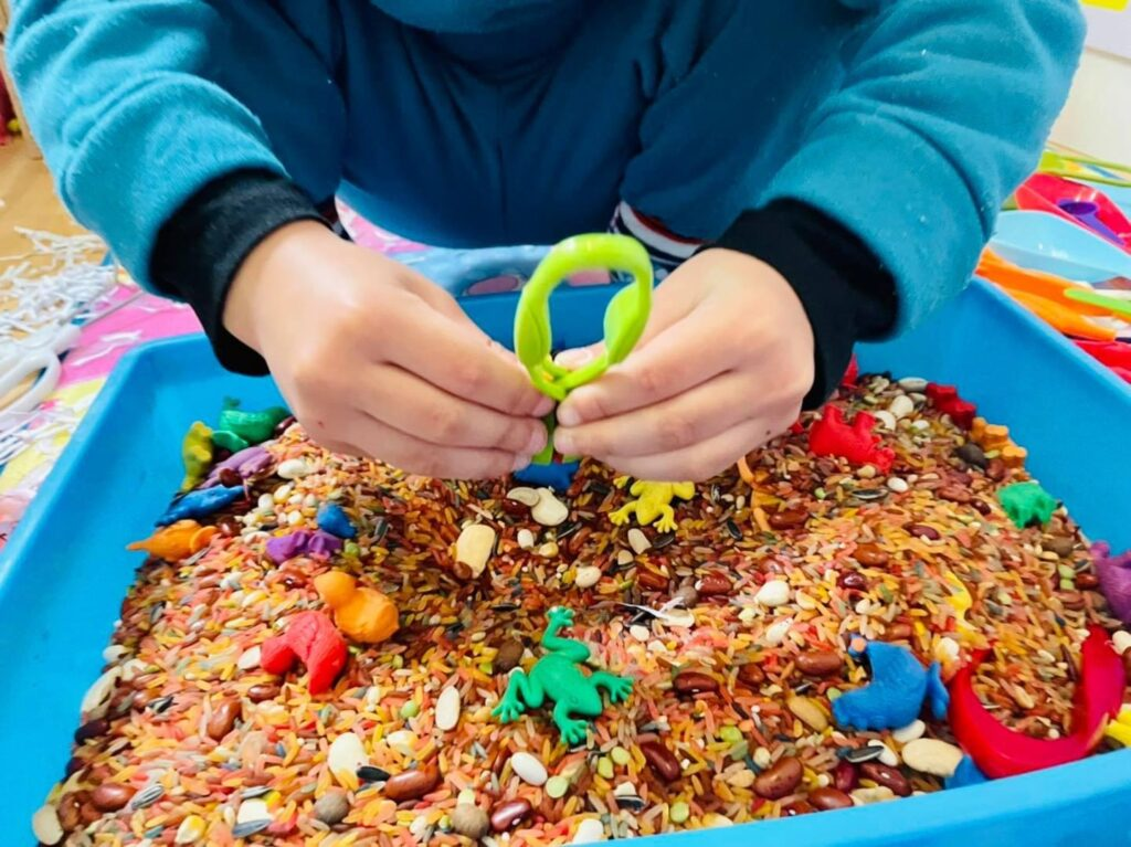 Closeup of a young child playing with sensory toys in a box