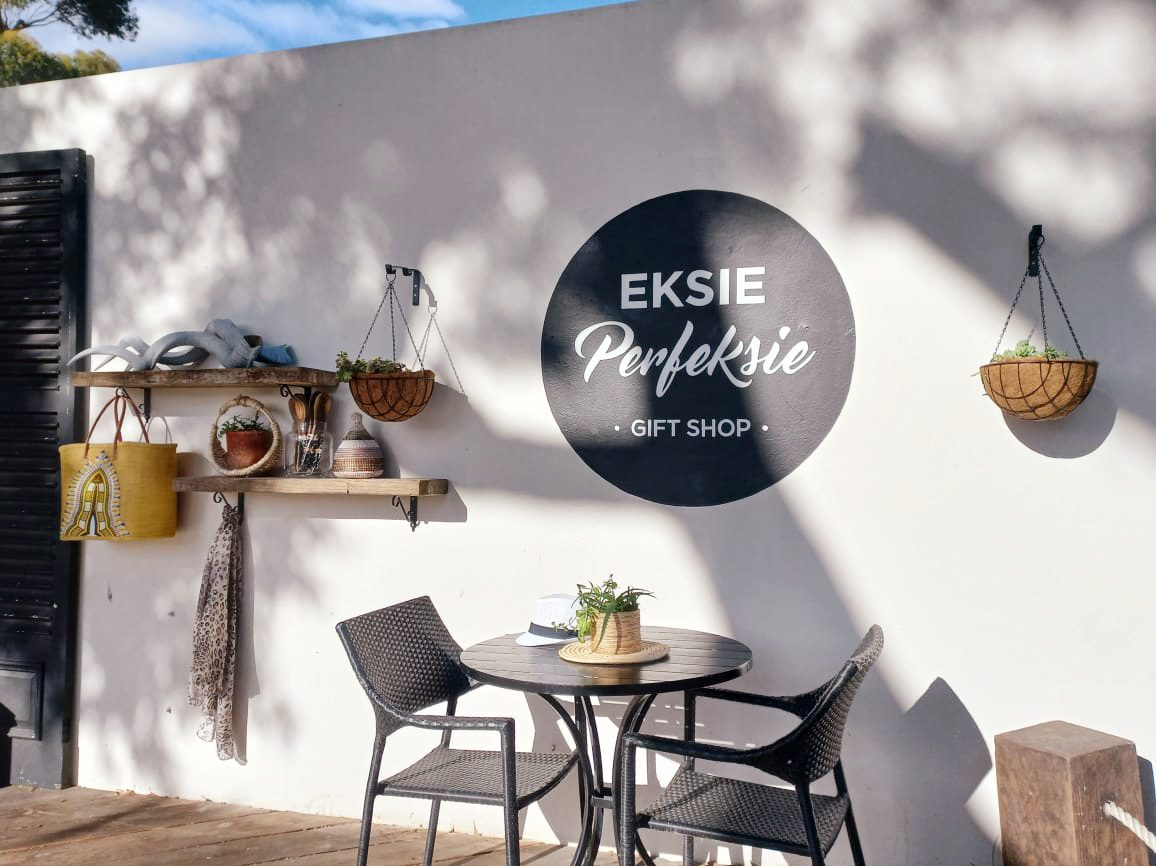 Storefront of Eksieperfeksie Gift Shop with patio table against white wall