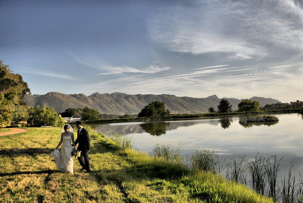 A married couple walking on grass next to a dam on Myrtle Grove Vine Estate