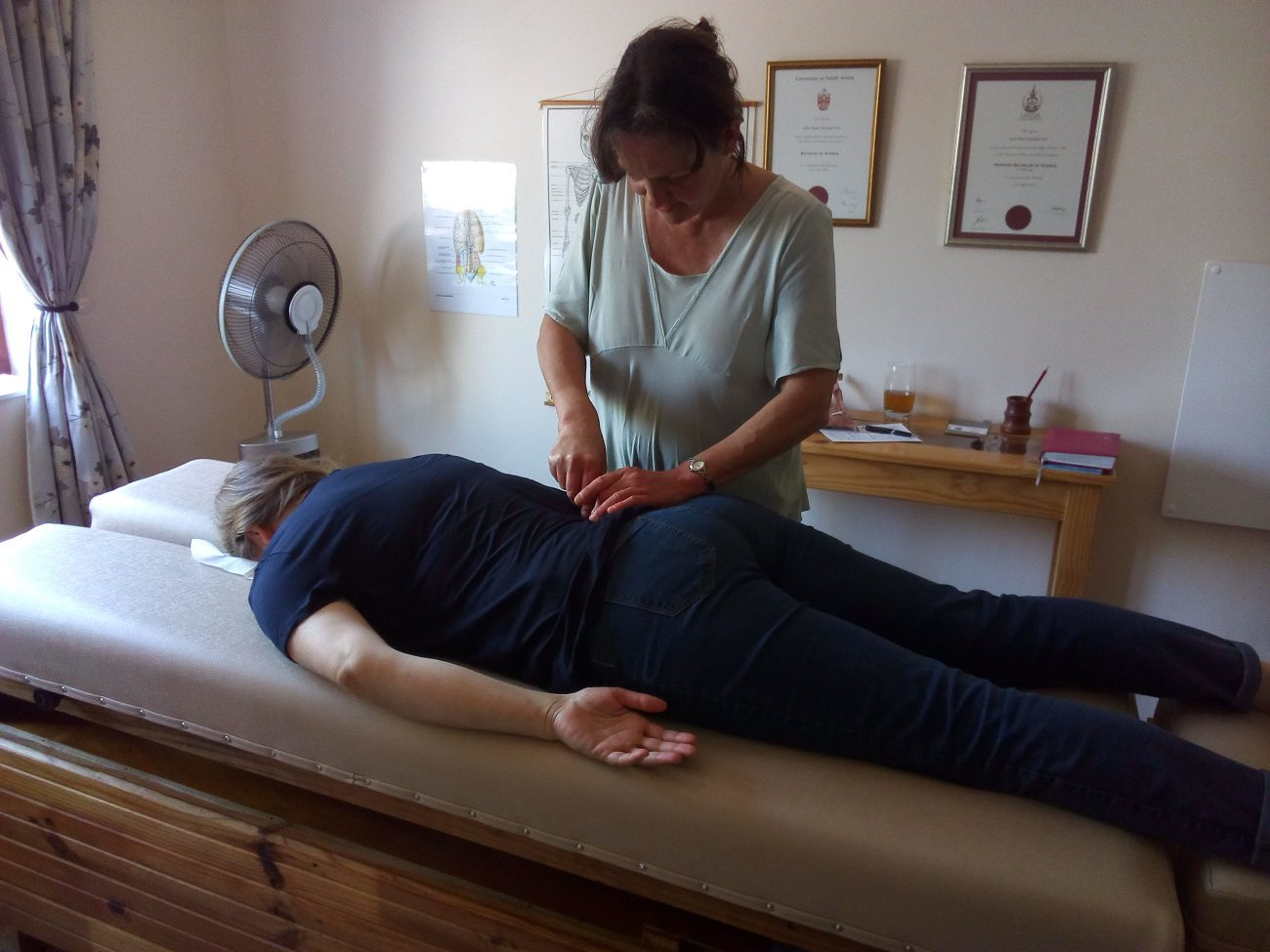 A neural pressure release practitioner giving a man lying on a massage bed a treatment